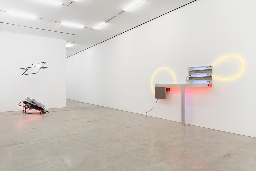 An installation view of a neon and aluminum Keith Sonnier sculpture and a kinetic and neon sculpture by Alice Aycock.
