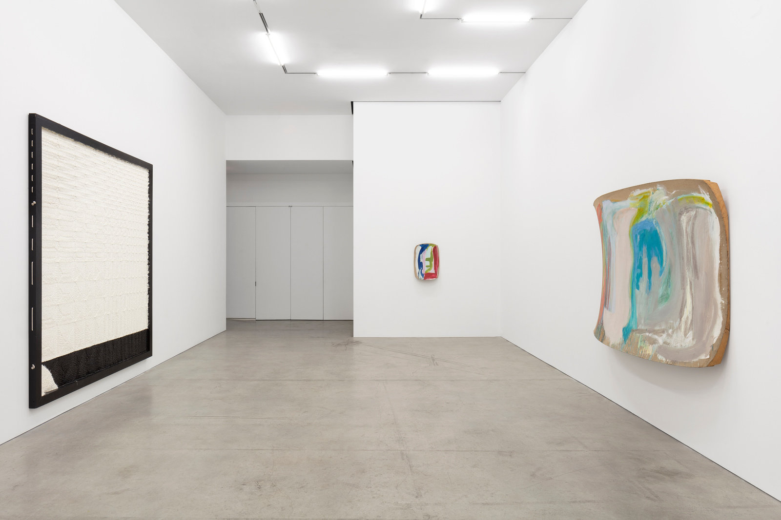 An installation view of three wall works: a black and white piece of Joe Zucker and two paintings by Ron Gorchov.