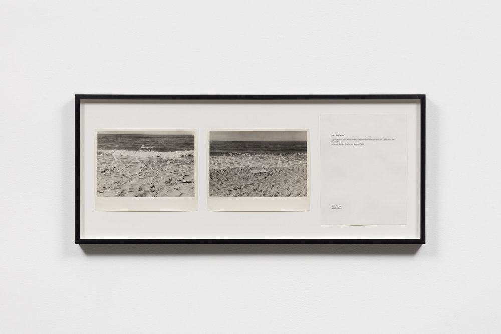 Two black and white photographs of the beach beside a white piece of paper with text, all hung in a black frame, by Robert Barry.