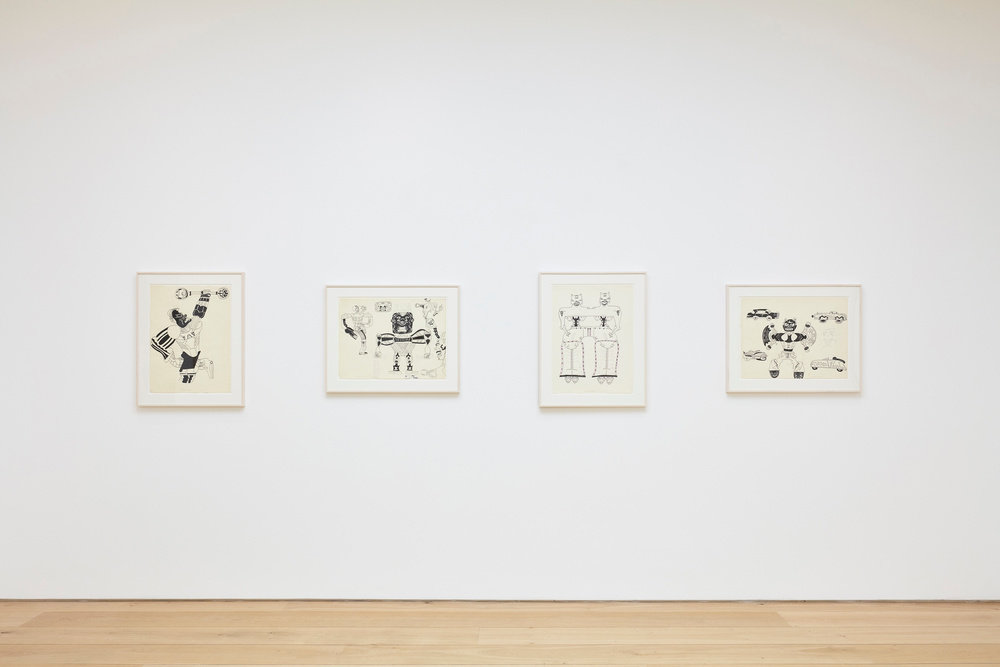 An installation view of four Karl Wirsum framed ink works on paper hanging on a wall horizontally.