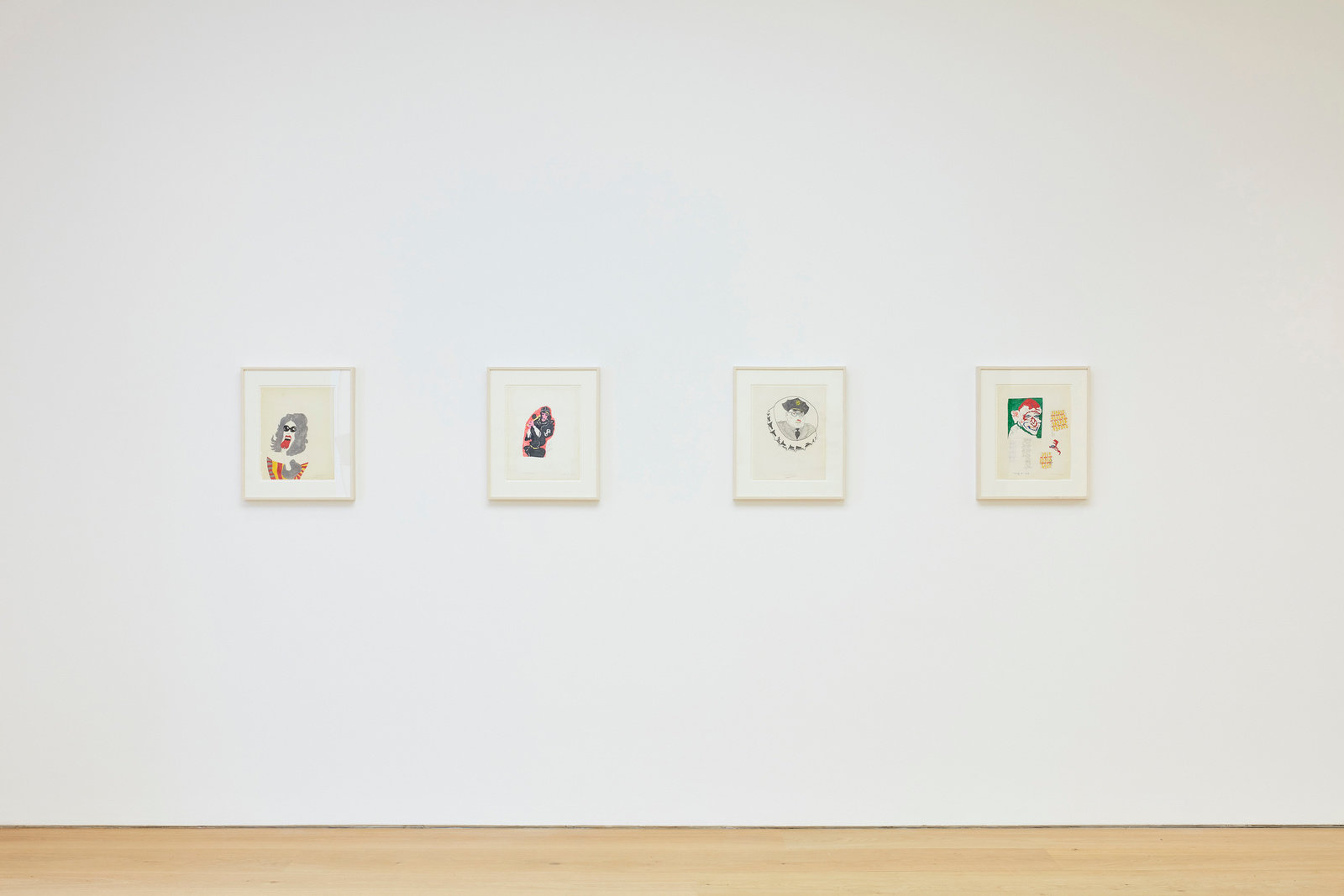 An installation view of four Karl Wirsum framed works on paper hanging on a wall horizontally.