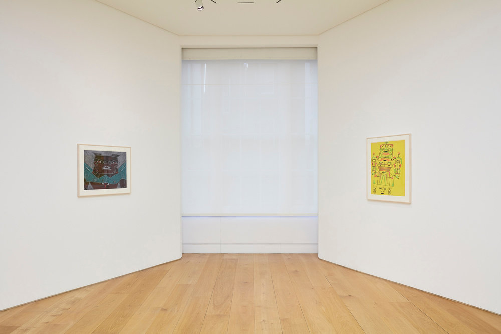 An installation view of two Karl Wirsum framed works on paper on two opposite walls.