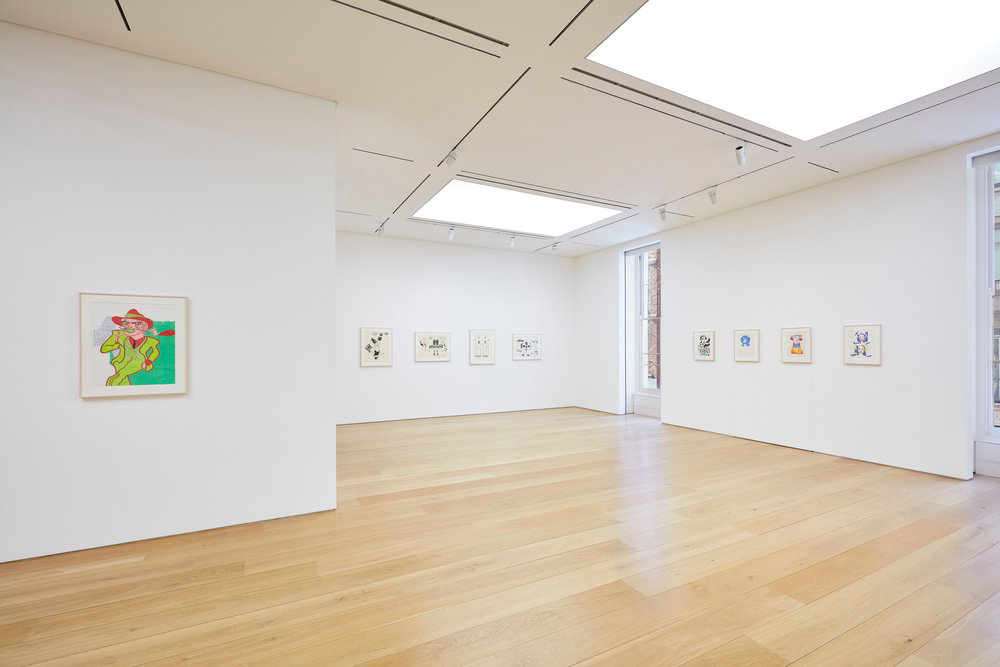 A partial view of nine Karl Wirsum framed works on paper hanging in the gallery.