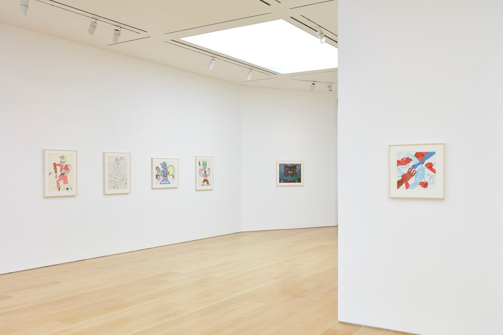 A partial view of five Karl Wirsum framed works on paper hanging in the gallery.