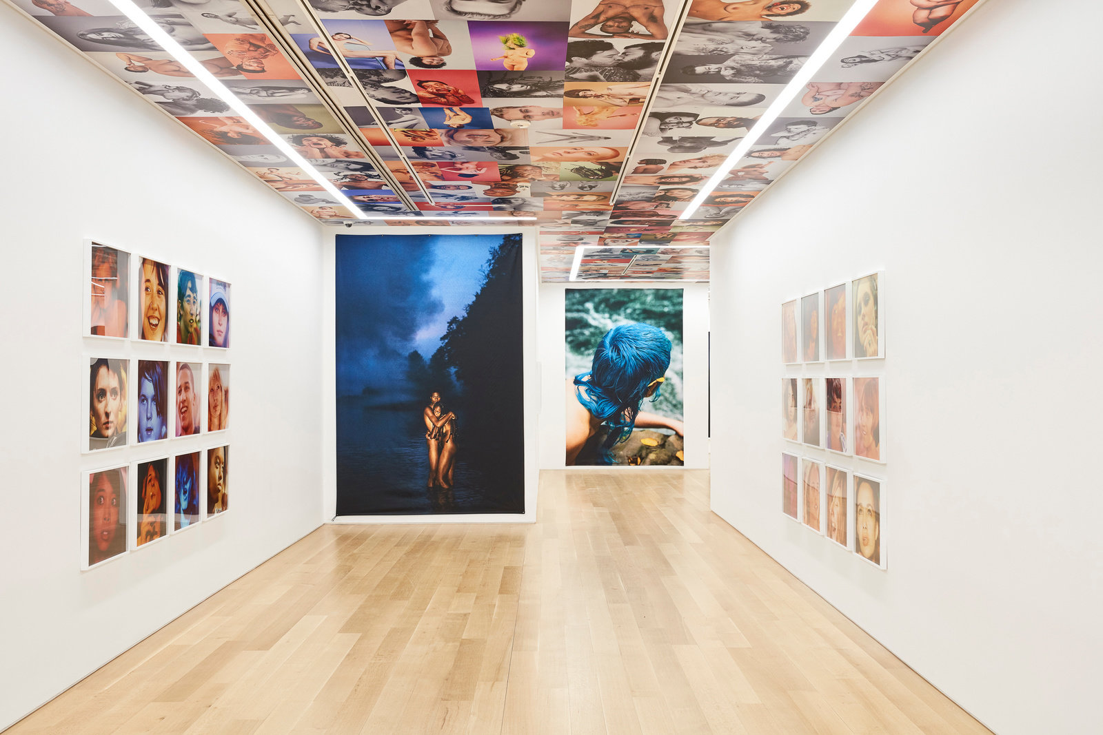 An installation view of Ryan McGinley photographs on the gallery walls and ceiling.