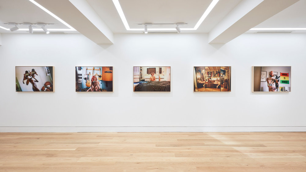 An installation view of five Ryan McGinley photographs hung horizontally on the wall.