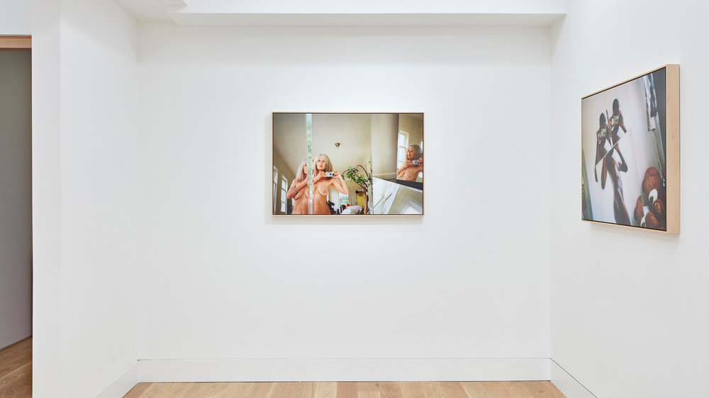 An installation view of two Ryan McGinley photographs hung on the wall.