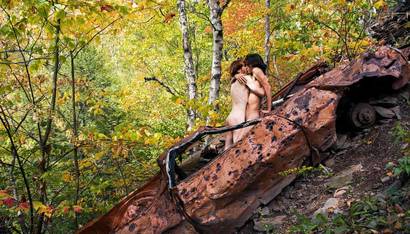 a gay couple kisses on top of a rusty car in the middle of the forest